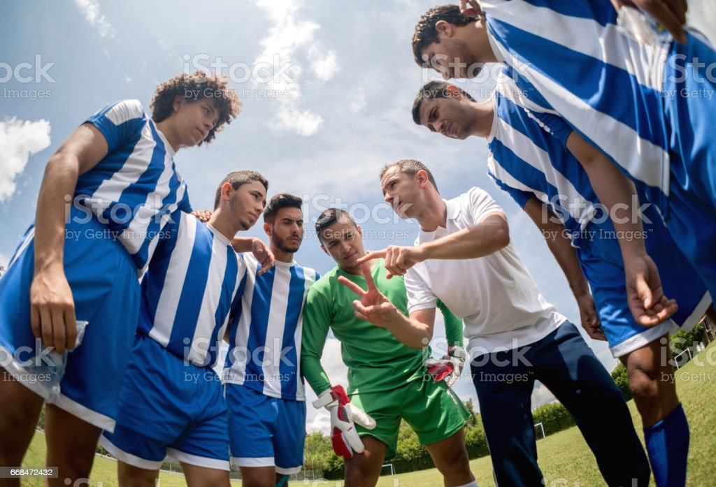 Coach talking to a group of soccer players stock photo