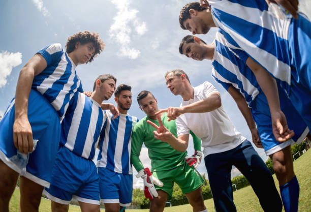 coach talking to a group of soccer players - coach stock photos and pictures