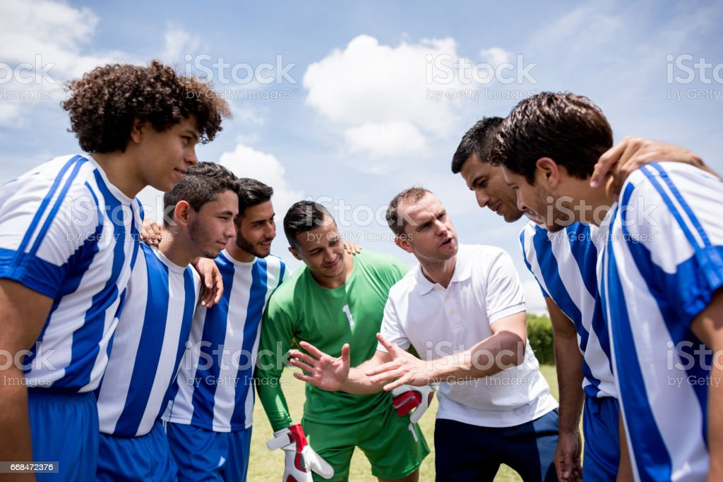 Coach talking to his players about tactics for the match stock photo