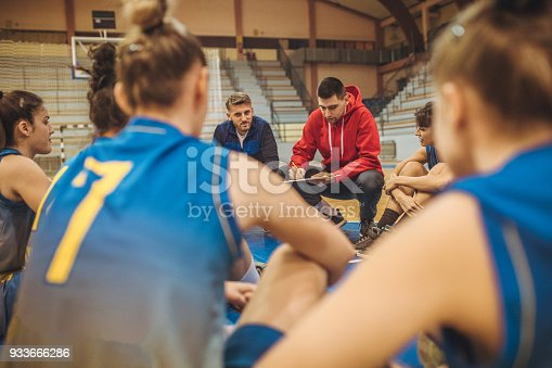 Group of women listening their coach on the floor before basketball training.