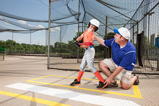 Coach Teaching Youth League Baseball in Cage stock photo
