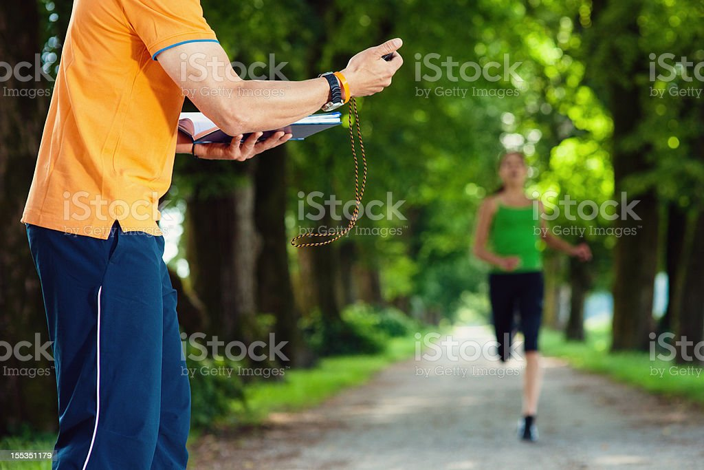 Coach Timing Young Female Sprinter stock photo