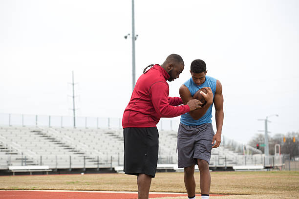 coach training a high school athlete for football. - coach stock photos and pictures