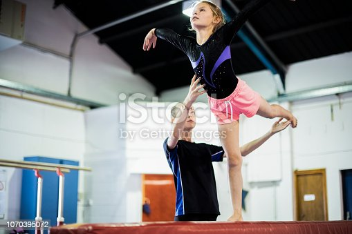Coach training young gymnast to balance on a balance beam