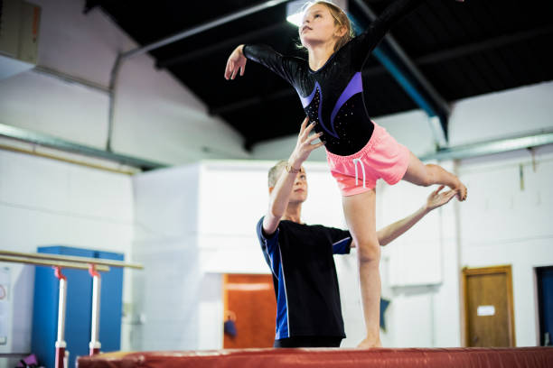coach training young gymnast to balance on a balance beam - gymnastics stock pictures, royalty-free photos & images