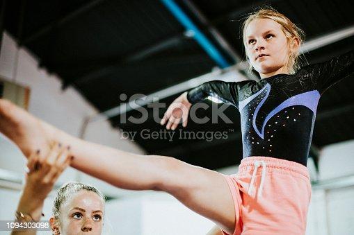 Coach training young gymnast to balance on a balance beam