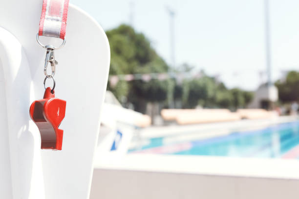 Coach whistle near swimming pool. Coral Coach whistle near outdoor swimming pool Horizontal. Coral lifeguard stock pictures, royalty-free photos & images