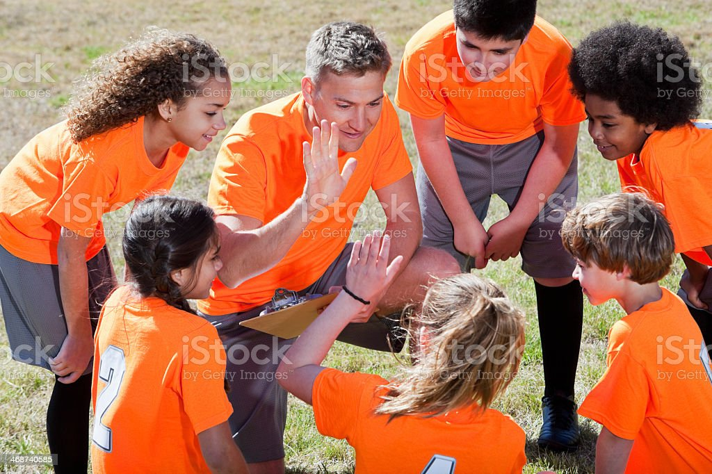 Coach with team of children in sports uniform, in huddle with...