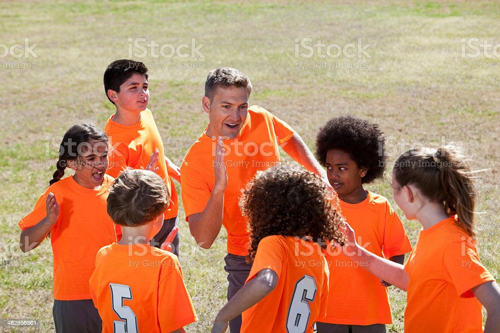 Coach with team of children in sports uniform, giving high five.