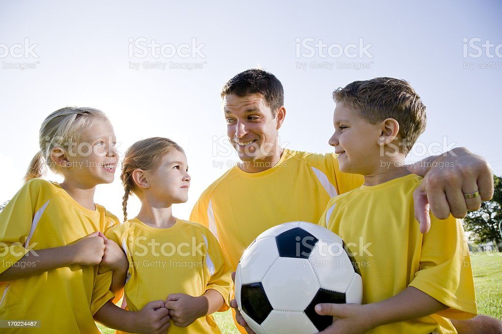 Coach with soccer ball and team of young children stock photo