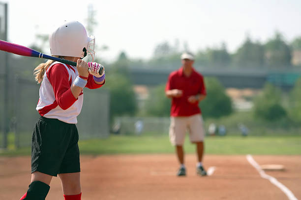 coached from third base - softball stock photos and pictures