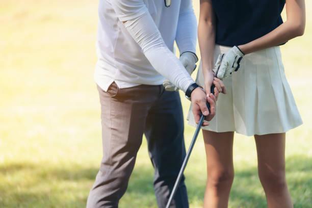 コーチはゴルフをプレーし始めてで木材をキャッチするゴルファーを教えています。 - ゴルフ ストックフォトと画像