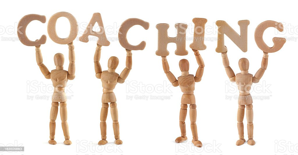 Coaching - wooden mannequin holding this word royalty-free stock photo