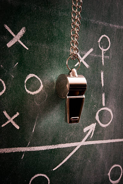 Coach's whistle hanging from a board on top of the game plan stock photo