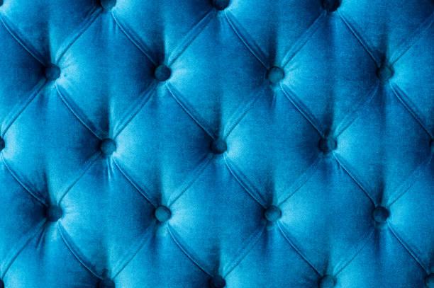 trainer-typ velours estrich angezogen mit knöpfen. blaue chesterfield stil gesteppte polsterung kulisse hautnah. textur-hintergrund - patchworkstoffe stock-fotos und bilder