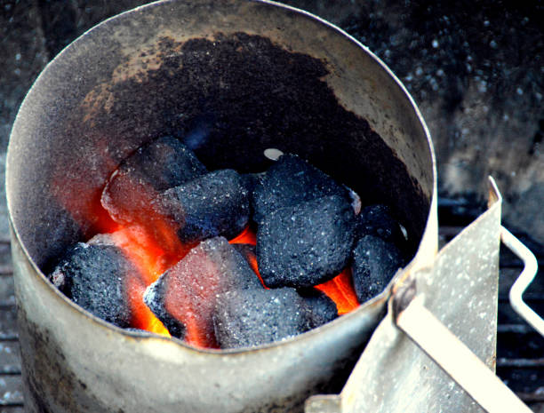 Coal briquettes burning in chimney starter stock photo