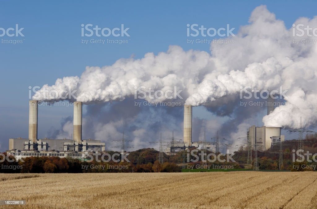 Coal burning power plant with stubble field in foreground stock photo