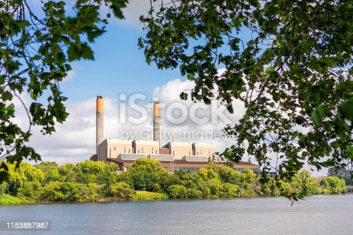 Leaves in the foreground around a coal-fired power station located on the banks of the Waikato River near Huntly in New Zealand.