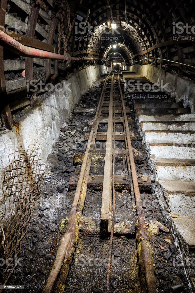 Coal mine underground corridor with stairs and railroad track