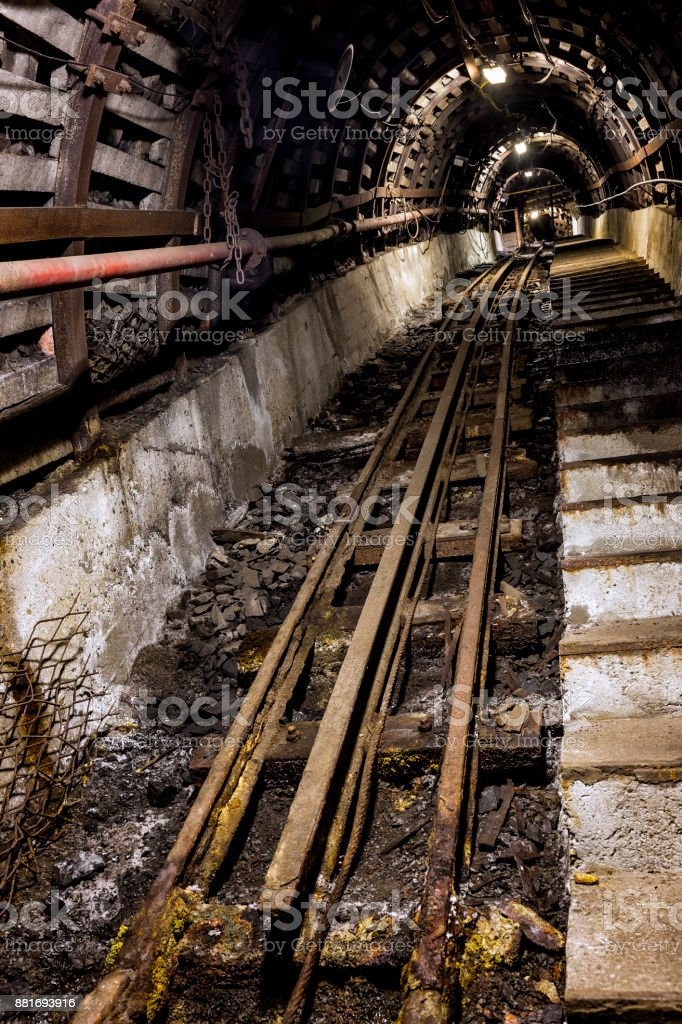 Coal mine underground corridor with stairs and railroad track,...