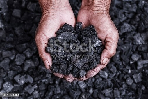 Coal mining - coal miner in the man hands of coal background. Picture idea about coal mining or energy source, environment protection. Industrial coals. Volcanic rock.