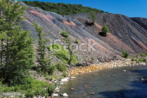 Coal mining waste spoil pile beside a stream with orange rocks showing environmental damage from the effects of legacy pollution and acid mine drainage. Also known as a spoil tip or boney pile; Pennsylvania, PA, USA.