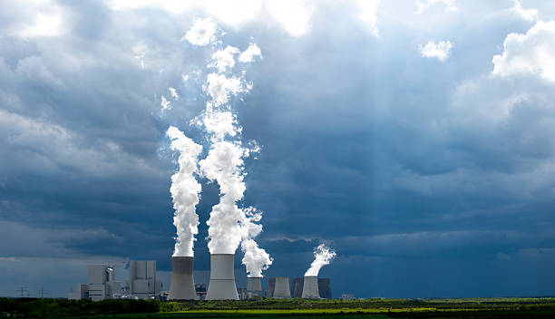 Coal-fired power plant and white steam against dark sky. stock photo