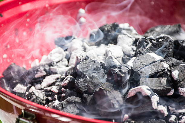 BBQ coals smoking before the grill is put on stock photo
