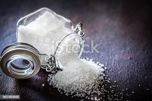 High angle view of a glass container filled with coarse grained sea salt laying on a rustic table. The container is tilted on the table and the salt is spilled out from it. Predominant colors are brown and white. The composition is at the left of an horizontal frame leaving useful copy space for text and/or logo. Low key DSRL studio photo taken with Canon EOS 5D Mk II and Canon EF 100mm f/2.8L Macro IS USM