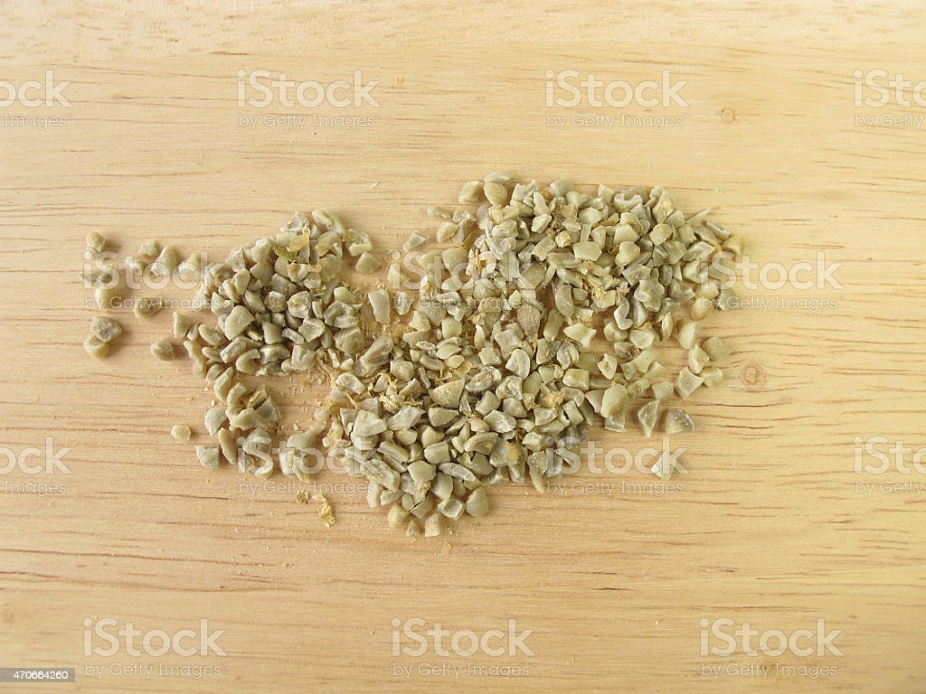 Coarsely ground green coffee beans stock photo
