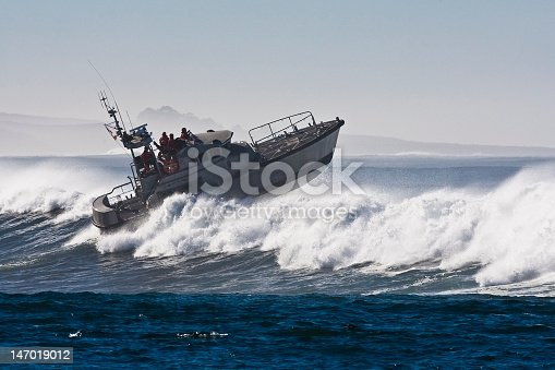 Coast Guard boat (identifying marks removed) battles storm waves during open ocean water rescue survival maneuver near Morro Bay, CA, off the west coast of the USA.