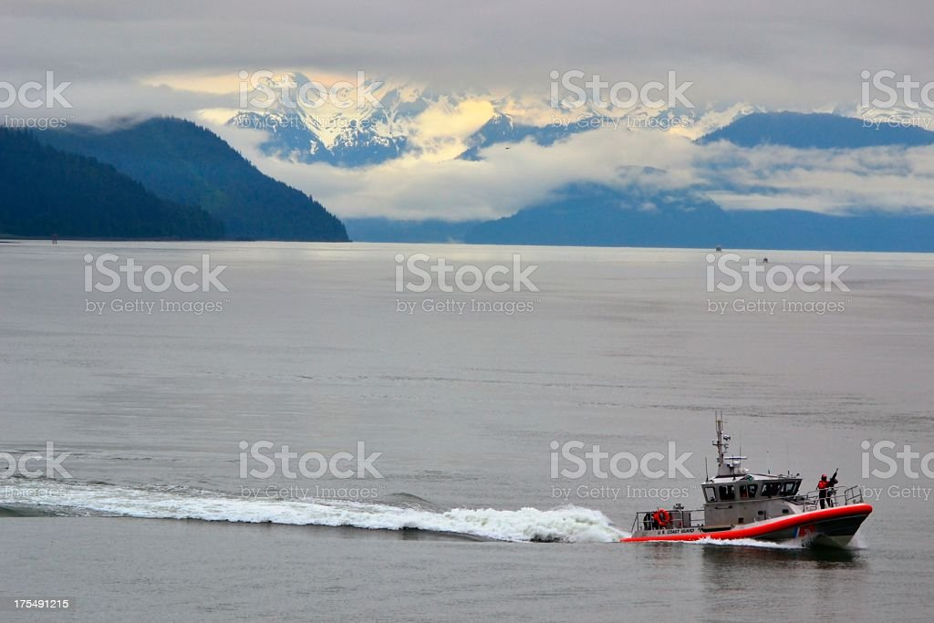 U.S. Coast Guard Boat Gunner on Front in Alaska Waters royalty-free stock photo