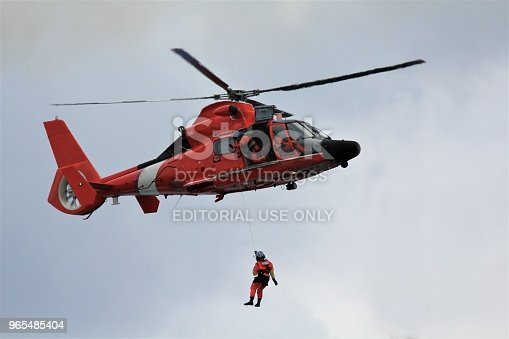 At sea in the Gulf of Mexico – February 3, 2018: A Coast Guard Rescue Swimmer is lifted back to their helicopter after a basket recovery of an emergency medical patient from a cruise ship.