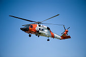Sikorsky HH-60J Jayhawk flying with clear blue sky as background.