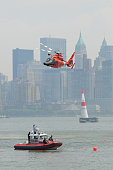 New York City, USA - June 20, 2010: US Coast Guard Helicopter hovering above  US Coast Guard boat with crew members as part of a demonstration to the public and spectators, as part of the Red Bull Air-Race worldwide series of competitions. Images were taken during the 2010 season from the NJ city coast side of the Hudson river.