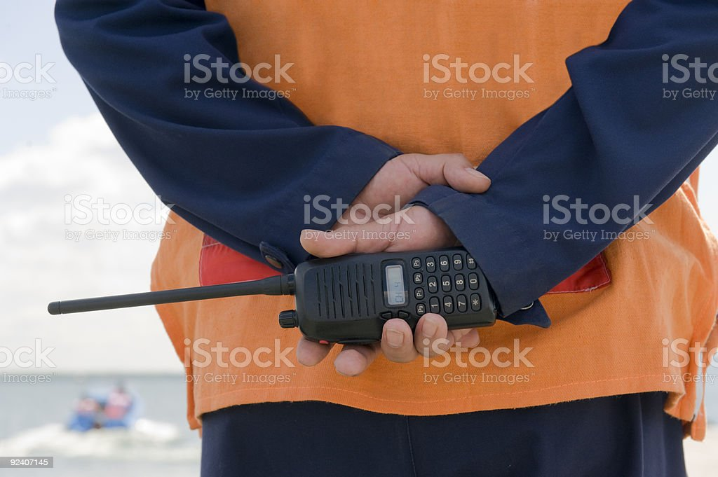A coast guard on duty holding a walkie-talkie stock photo
