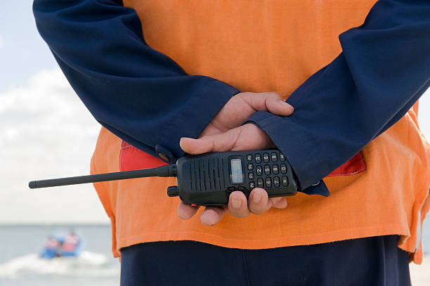 A coast guard on duty holding a walkie-talkie Monitoring of a coastal line customs official stock pictures, royalty-free photos & images