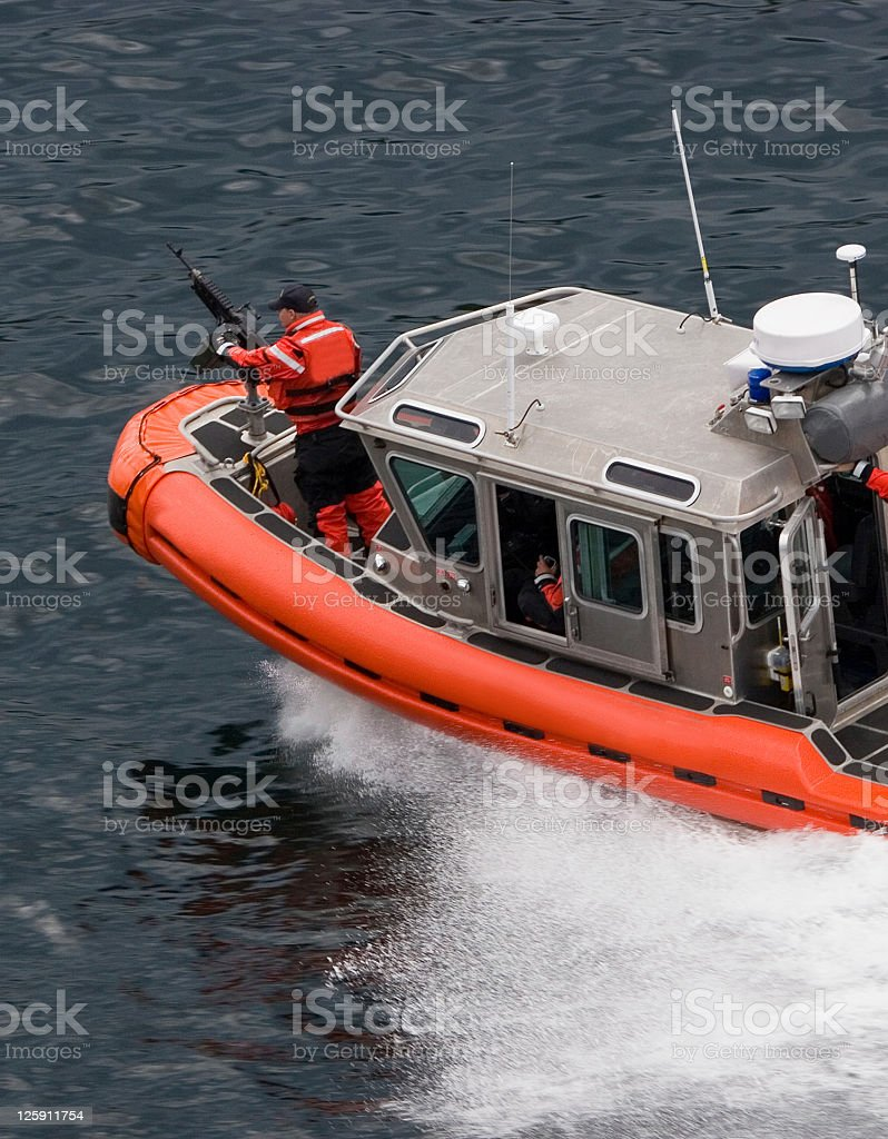 Coast Guard on Zodiac with Machine Gun royalty-free stock photo