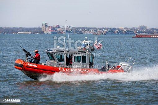 New York, March 8, 2014 – US Coast Guard boat patrolled NY harbor near Statue of Liberty.