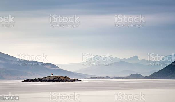 Photo of Coast of Norway sea. Clouds of haze. Beacon on rock
