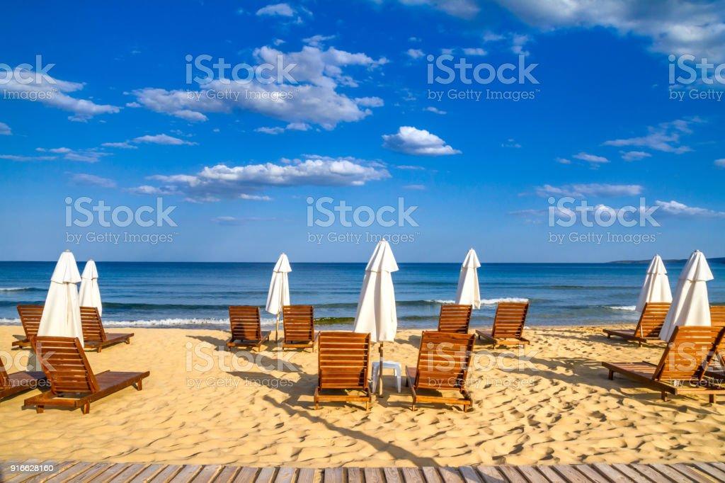 Coastal landscape - Beach umbrellas and loungers on the sandy seashore stock photo