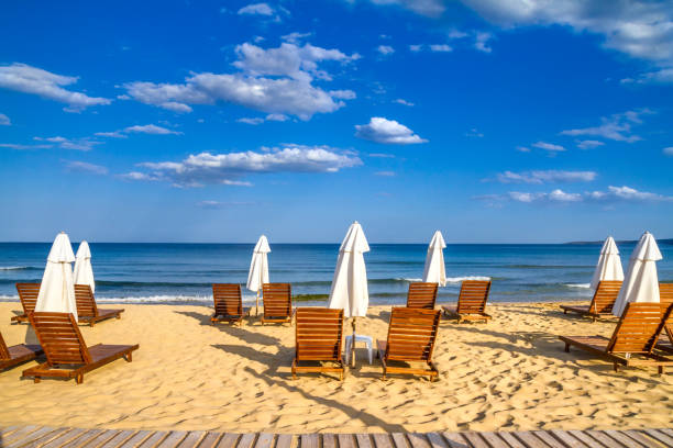 Coastal landscape - Beach umbrellas and loungers on the sandy seashore Coastal landscape - Beach umbrellas and loungers on the sandy seashore, the Kavatsi bay near city of Sozopol in Bulgaria bulgaria stock pictures, royalty-free photos & images