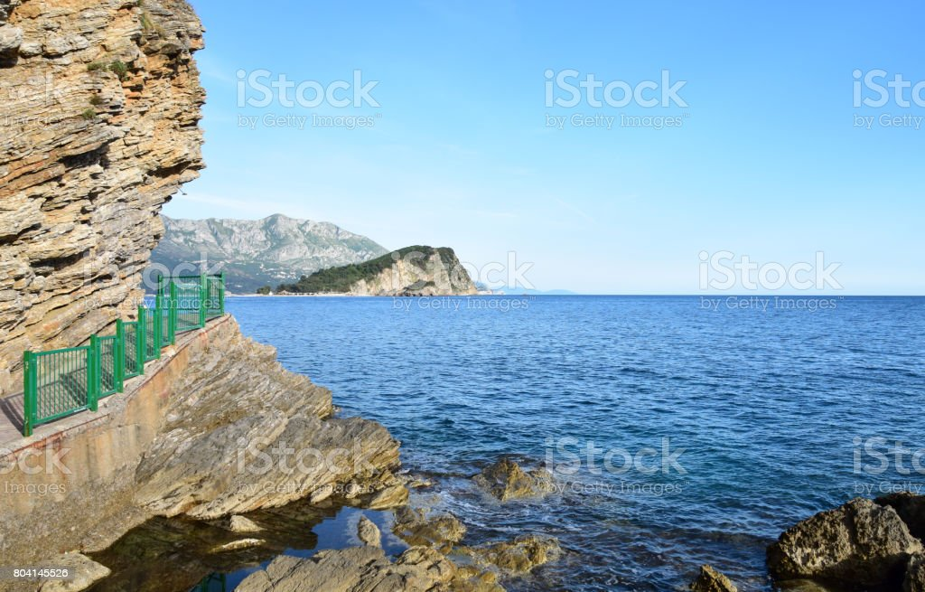 Coastal landscape - protective fence next to walking trail along the cliffs stock photo
