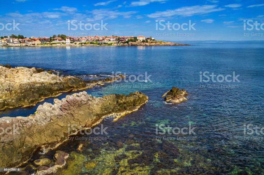 Coastal landscape - the rocky seashore with houses under the sky with clouds stock photo