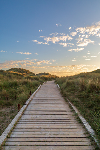 A wooden pathway leading towards the sea at Formby in Merseyside, taken at sunset