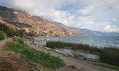 istock Coastal road along lake Atitlan with pier along mountainrange at Panajachel, Guatemala 1290411396