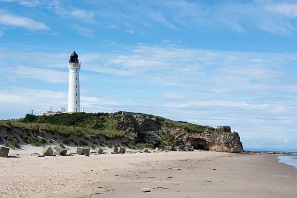 Coastal Scene with lighthouse and sea caves stock photo