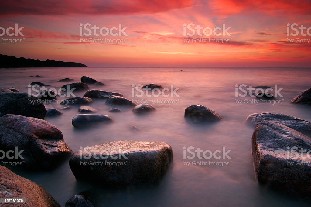 Coastal Sunset moody nightfall an a rocky shore  Backgrounds Stock Photo