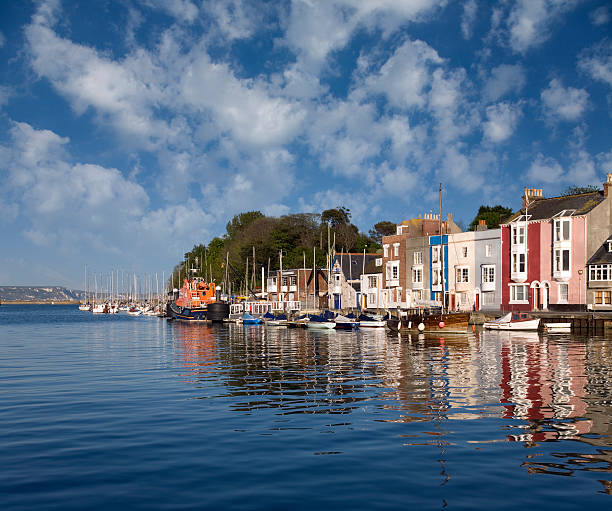 coastal view from the water of weymouth harbour on sunny day - weymouth stock photos and pictures