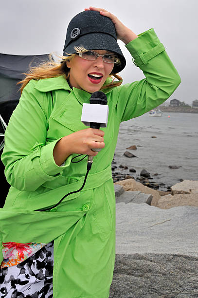 coastal weather reporter braving the wind - mike cherim stock pictures, royalty-free photos & images